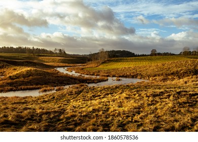 Curved river flowing through rural landscape. Morning sun lights the scen with very warm colors and nice clouds in the background