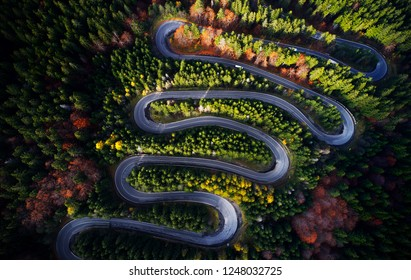 Curved road trough the colorful autumn forest; pass in Transylvania Romania, aerial view from drone