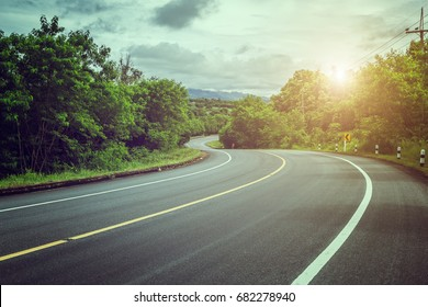Curved road,trees and grass on roadside. landscape with sky and sun.