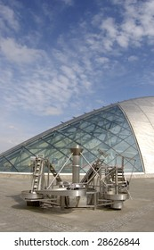 The curved roof and window of the Glasgow Science Centre with a working exhibit in the foreground