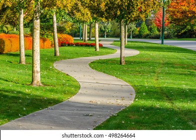 Curved sidewalk, path, trail at the empty street. Neighborhood scenery.