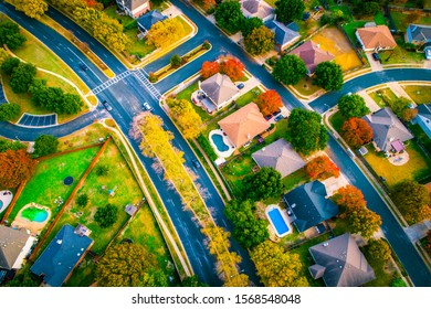 curved streets in suburbia development straight down drone views fall Autumn suburb suburbia round Rock Texas colorful landscape trees changing colors fall in central texas