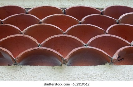 Curved terracotta roof tiles as an insert in a wall seen from below