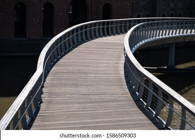 Curved wooden walk way leading across a water way river