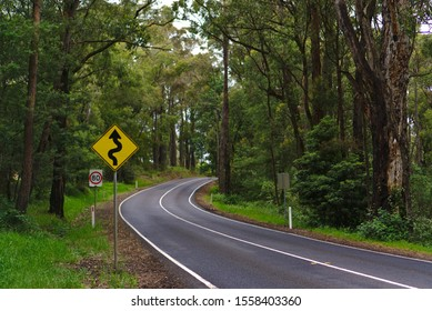 Curves and bends sign in yellow and black color on side of the road