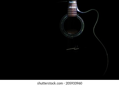 curves of a black body guitar lit - focus on the rosette