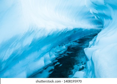 Curves of ice melted down by a winding river through the Matanuska Glacier. Multiple levels form a series of shelves and block the sun from inside the canyon.