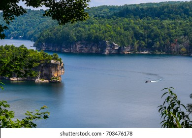 Curves in Summersville Lake in the mountains of West Virginia as a boat passes making a curved wake in the curve of the lake