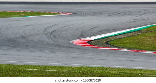 Curving asphalt red and white kerb of a race track detail. Motorsports racing circuit close up with tire mark.