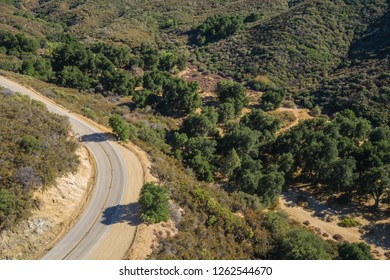Curving asphalt road winds around the corner of a California hillside.
