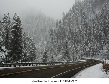 curving blacktop road through the mountains in winter