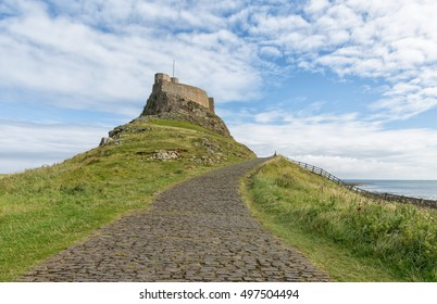 The curving cobbled road leading to Lindisfarne Castle on Holy Island, Northumberland, England.