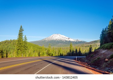Curving highway with a dramatic view of Mt. Bachelor and beautiful green pine tree forest near Bend, Oregon
