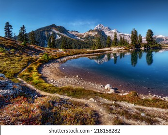 Curving mountain lake shore with perfect reflection, blue sky, and distant mountains