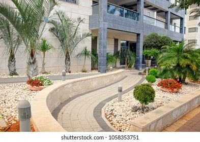Curving passageway to the entrance of the living modern building tiled with yellow stone slabs. Taken in Ness Ziona, Israel
