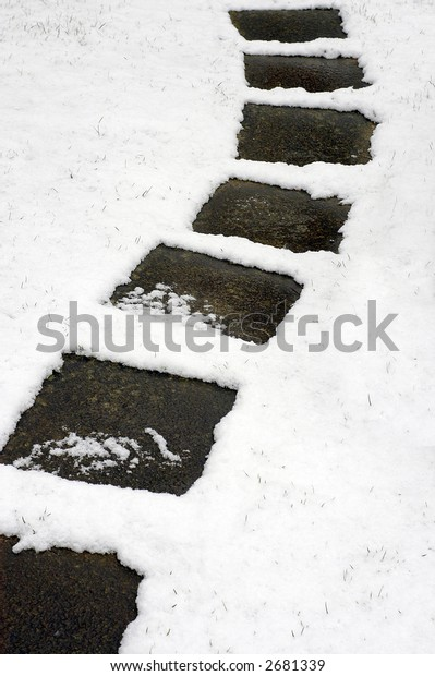 A curving path of square paving stones through a covering of light snow
