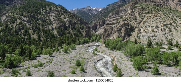 Curving river flows out of the mountains into the natural wilderness of Wyoming.