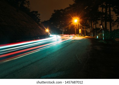 Curving road at the base of the mountain leading into the distant, multicolors traffic light trails with motion blur effect. Night time long-exposure landscape of Dalat, Vietnam