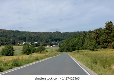 Curving road between fields and trees in Germany Langgöns in sommer