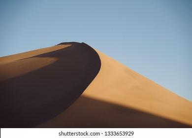 The curving sand dunes of the gobi desert at sunrise.