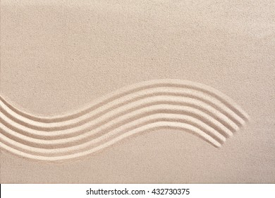 Curving wave pattern raked into smooth manicured sand in a Japanese zen garden for meditation and tranquility with copy space above