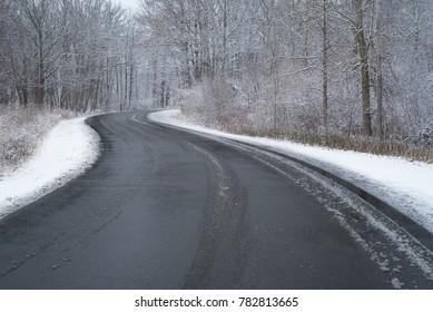 curvy black road on snowy morning