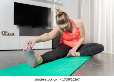 Curvy, blonde Caucasian woman practicing sport at home in a quiet and smiling way.
