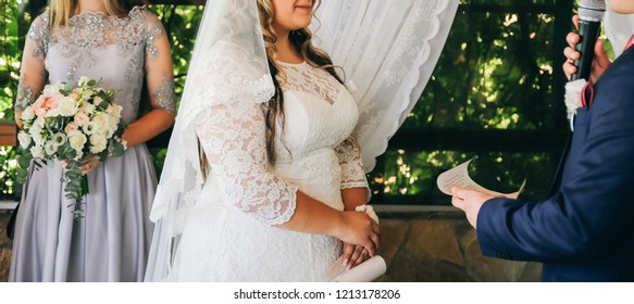 Curvy bride in white lace dress and a groom. Wedding couple at the ceremony. Man and wife giving marriage vows. Engagement rings. Outdoors flowers decoration.