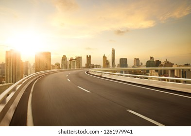 Curvy flyover highway moving forward road with Bangkok cityscape sunrise scene view . motion blur effect apply