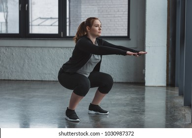 Curvy girl doing squat in gym