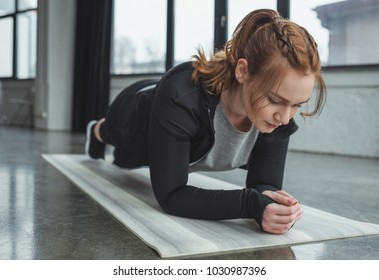 Curvy girl in gym standing in plank