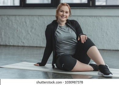Curvy girl sitting on floor and looking at camera in gym