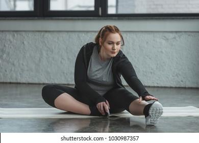 Curvy girl stretching on floor in gym