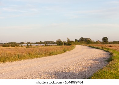 Curvy gravel country road on summer evening in Bauska, Latvia
