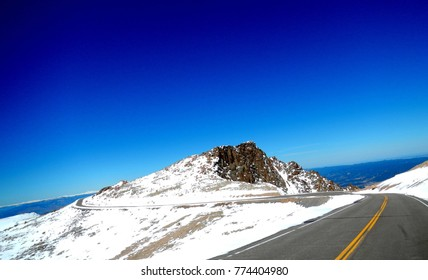 Curvy Mountain Road On Top of Snow Covered Peaks