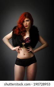 Curvy redhead woman posing in sexy lingerie isolated on gray background