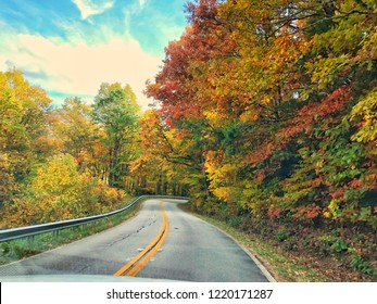 Curvy road to the Chattahoochee National forest park with fantastic colorful leaves changing in Fall season on the background of blue sky with white clouds, Autumn in North GA USA.
