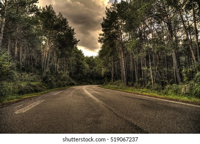 A curvy road at a cloudy day going through a forest in spain