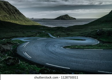 a curvy road down a green hill surrounded by grass fields heading to the ocean with an island in the center of the frame and a dramatic sky on the Faroe Islands during sunset