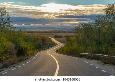 Curvy road leading to a valey at the sunset