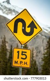 Curvy road sign an 15 m.p.h speed limit