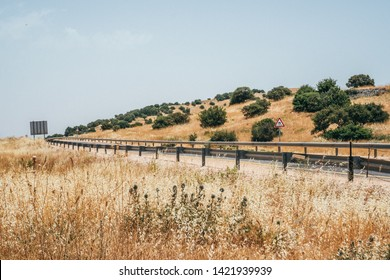 Curvy road surrounded by dry landscape in Golan Heights, Israel.