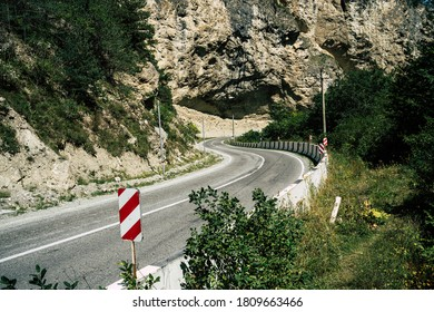 Curvy road with traffic signs in mountains. Red diagonal keep left obstacle traffic sign placed on stone border of curvy asphalt road going through mountainous terrain