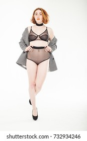 curvy size plus red hair model woman in lingerie and jacket at studio white background