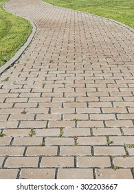 Curvy urban path in a park made with cobbles