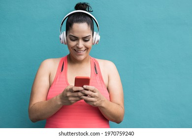 Curvy woman listening playlist music using mobile phone after jogging routine outdoors - Focus on face