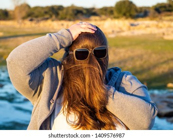 A curvy woman making funny gestures with hair in front of his face and sunglasses
