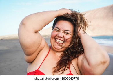 Curvy woman smiling on camera wearing bikini with beach in background - Plus size and overweight female body concept