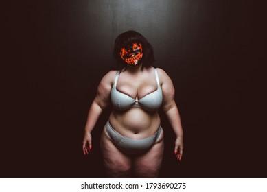 Curvy woman wearing demon mask. Fine art concept