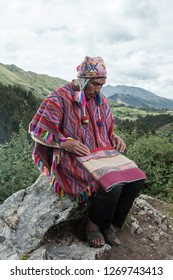 Cusco, Perú - Circa May 2018; Peruvian quechua man holding textile, nature background